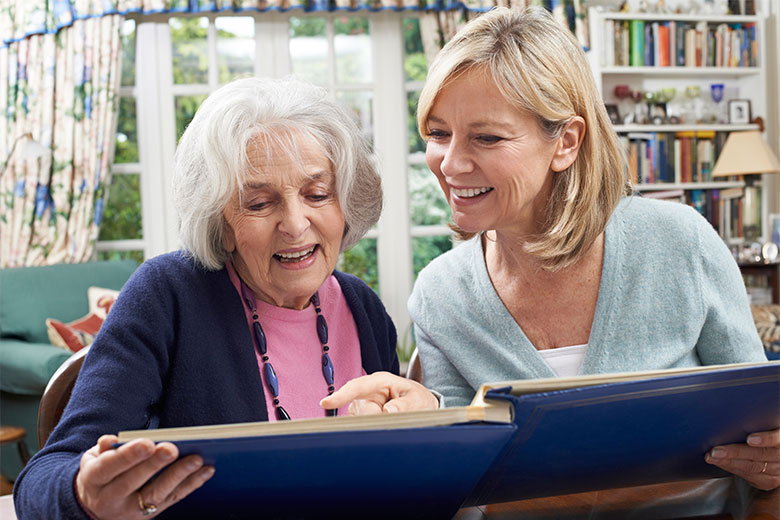 Memory Care staff looking through photo album with senior woman