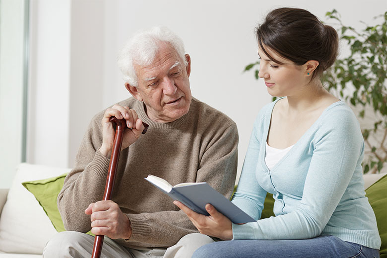 Caregivier reading to senior man